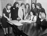 Group of women looking at a pattern book.