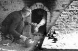 Two men unloading fired pottery from kiln.