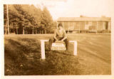 Sailor sitting on top of sign, circa 1940