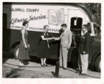 Caldwell County Library bookmobile from the side with two men and women