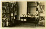 Black Mountain Library interior with bookshelves and table piled with books