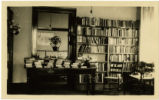 Black Mountain Library interior with bookshelves and table piled with books and baskets of flowers
