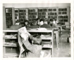 Thomasville Public Library reference department full of seated patrons, one of which is reading a...