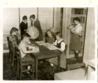 Harnett County Library interior with children reading, and woman helping a young man