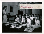 Woman teaching classroom of seated children behind table of books, Richmond County