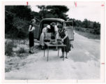 Women browse books on bookmobile parked on side of dirt road, Richmond County