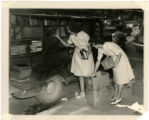 Miss Julie Vanderipe (right) and Miss Ruth Massey prepare Olivia Raney bookmobile for service
