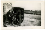 Boys (one on bicycle) and women browse books in bookmobile parked outside Grover Hood Store