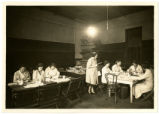 Women seated at tables, mending books in Forsyth County as part of the WPA book mending project,...